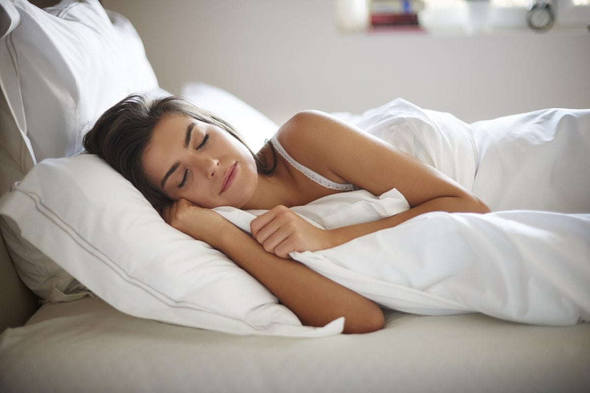 Young woman sleeping in bed - Annette Sloly Hypnotherapy